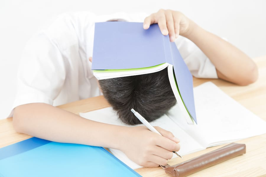 本で頭を抱える男子学生