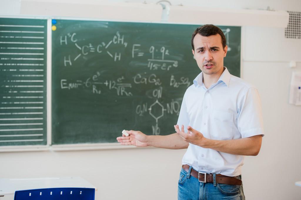 若い男の先生が教室の黒板の前で話す