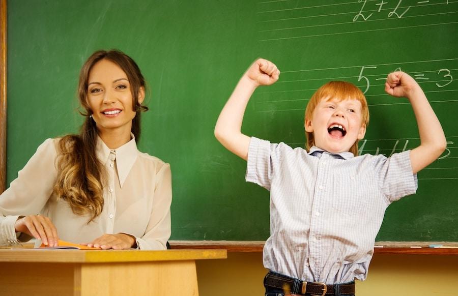 little happy redhead boy answering near blackboard in school - 塾選びの大切なポイント!その先生はお子様の恩師になれますか?