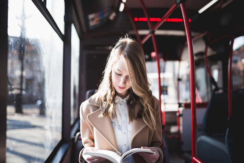 Beautiful-young-woman-sitting-in-city-bus-and-reading-a-book