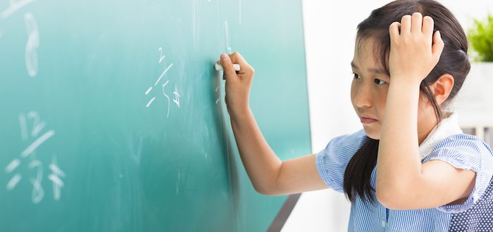 school-girl-doing-math-problems-on-the-chalkboard